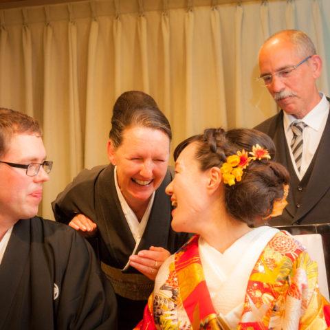 笑い合う新郎新婦と親族