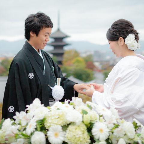 八坂の塔を背景に、指を贈り合う新郎新婦