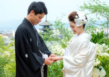 八坂の塔を背景に、花嫁に指輪を贈る花婿の様子