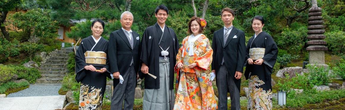 庭園を背景とした和装の新郎新婦と親族の記念写真